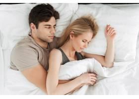 沉着英俊的夫妇睡在床上的肖像_6819601
