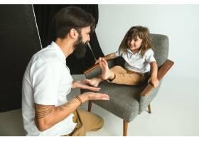 父亲和年幼的儿子在家里的起居室里玩耍年_13341330