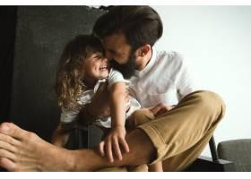 父亲在家里的起居室里陪着年幼的儿子玩耍_13056900
