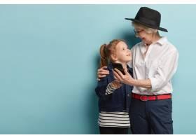 滑稽积极的老太太拥抱小孙女用现代手机拍_11579308