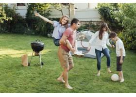 父亲让女儿骑在背上母亲和儿子在公园踢足_5127654