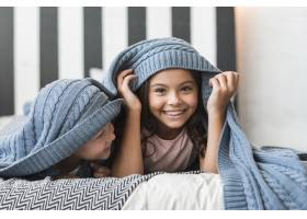 快乐的男孩看着他的妹妹躺在床上的毯子下_3299102