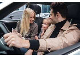 快乐的男人和他的妻子和女儿坐在车里_6873292