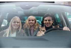 快乐的男人和他的妻子和女儿坐在车里_6873297