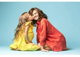 怀孕的母亲和十几岁的女儿蓝色背景上的家_7911251