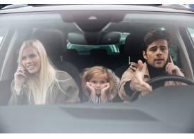 悲伤的小女孩坐在车里而她的父母在聊天_6873792