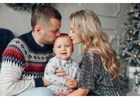 慈爱的父母用圣诞树亲吻婴儿头部的腰部照片_10936348