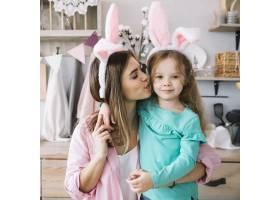 戴兔耳朵的妇女亲吻女儿的脸颊_3817265