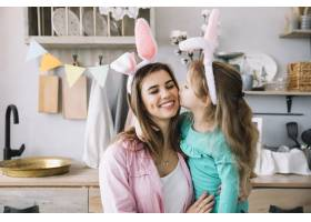 戴着兔子耳朵的可爱女孩亲吻母亲的脸颊_3817238