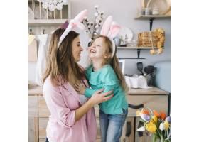 戴着兔子耳朵的小女孩和妈妈笑着_3817243