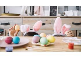 戴着兔子耳朵的母亲带着孩子躲在桌子后面_3831161