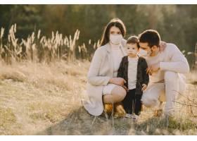 戴着口罩的时尚家庭走在春天的田野上_8355938