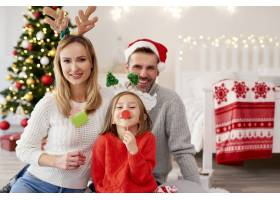 戴着圣诞面具微笑的一家人的肖像_11725847