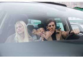 打哈欠的男人坐在车里睡着的妻子和女儿_6873796