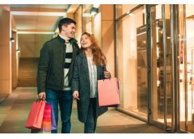 提着购物袋的幸福夫妇在城市里享受夜晚_8609472