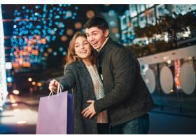 提着购物袋的幸福夫妇在城市里享受夜晚_9159440
