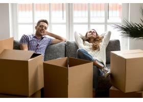 搬进新家后幸福的夫妇在沙发上放松_3953862