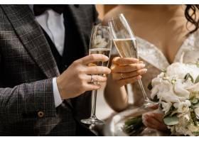 新人手持香槟酒杯和婚礼花束的前景_7497941