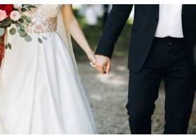 新娘和新郎手牵手站在拱门前_3984978
