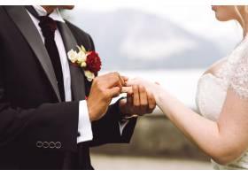 新娘把结婚戒指戴在新郎的手指上_3985020