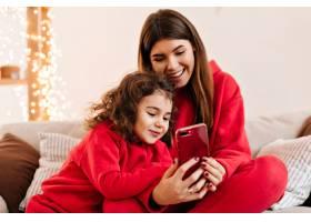 无忧无虑的黑发女人带着女儿使用智能手机_12431929