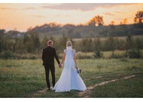日落时分婚礼结束后新娘和新郎在田野里_7899975