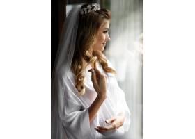 早晨戴着皇冠的金发新娘站在明亮的窗户前_3337309