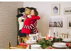 朋友们在圣诞晚餐前拥抱_1400591