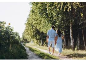 期待着男人和女人带着向日葵沿着穿过田野的_3339402