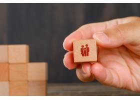 木桌侧视图上的家庭概念手持木质立方体_9486022