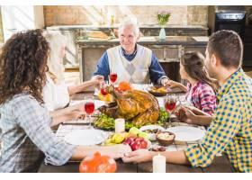 幸福的一家人在餐桌上手牵手拿着食物_3180724