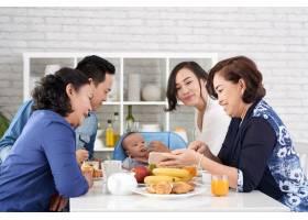 幸福的亚洲家庭坐在早餐桌上_5577367