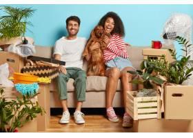 幸福的夫妇坐在沙发上狗被纸箱包围着_12607680