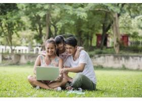 幸福的家庭父亲母亲和女儿坐在草地上在_2888909