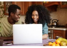 幸福的年轻非裔美国家庭坐在厨房餐桌前用_9437596