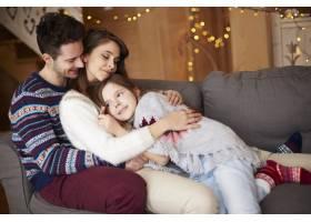 幸福的父母和女孩在沙发上放松_11757139