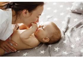 开心英俊的母亲和她刚出生的儿子玩耍亲吻_9696789