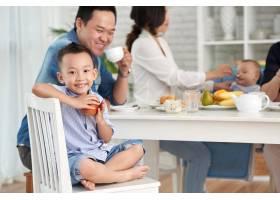 快乐的亚洲男孩与家人共进早餐_5577380