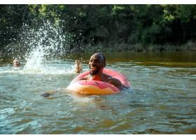 快乐的人一边笑一边在河里游泳玩得很开心_13457472
