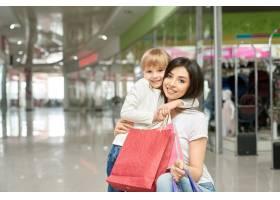 快乐的女人和女孩在购物中心摆姿势微笑_8792533