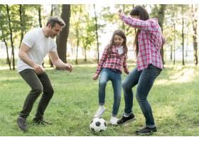 快乐的女孩和她的父母在公园的草地上踢足球_4958795