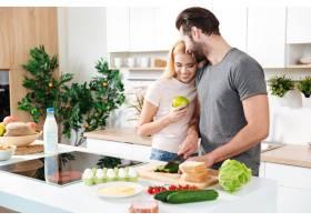 微笑的年轻情侣站在厨房做饭_8078522