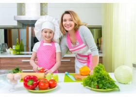微笑的年轻母亲和穿着粉色围裙的女儿在厨房_11177196