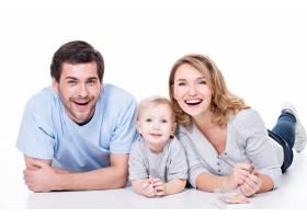 微笑的年轻父母带着年幼的孩子躺在地板上的_11554650