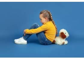 忧伤的小女孩孤零零地坐在蓝色背景上的肖像_13635737