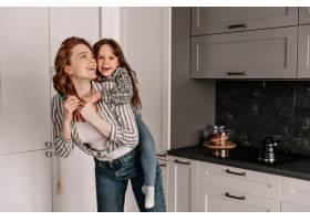 快乐的妈妈和女儿穿着相似的衣服在厨房里_12677628