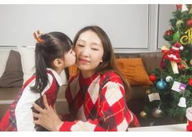 快乐的妈妈和小女儿在家里装饰圣诞树和礼物_11548042