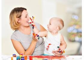 快乐的孩子在家里画他母亲的脸_10729957