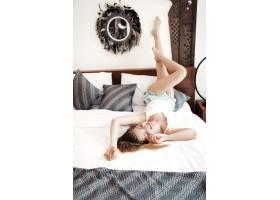 快乐的年轻女子抬起双腿躺在床上_13548985