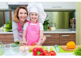 快乐的年轻母亲和穿着粉色围裙的女儿在厨房_11599237